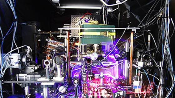 """Bei der Strontium-Gitteruhr werden die Atome in einem Gitter aus Licht zusammengehalten. Ihr Wechsel zwischen den Energieniveaus wird durch das intensive Laserlicht angeregt. Die Strontiumatome """"schlagen"""" mit 430 Billionen Mal pro Sekunde besonders schnell."""