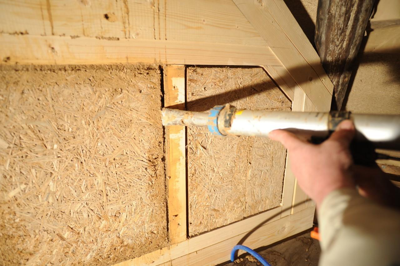 Einsetzen von Dämmplatten aus Rohrkolben in ein Fachwerk:Auch der Fugenmörtel wird aus Typha hergestellt. Die Masse dient dazu, die Bauteile winddicht zu machen.