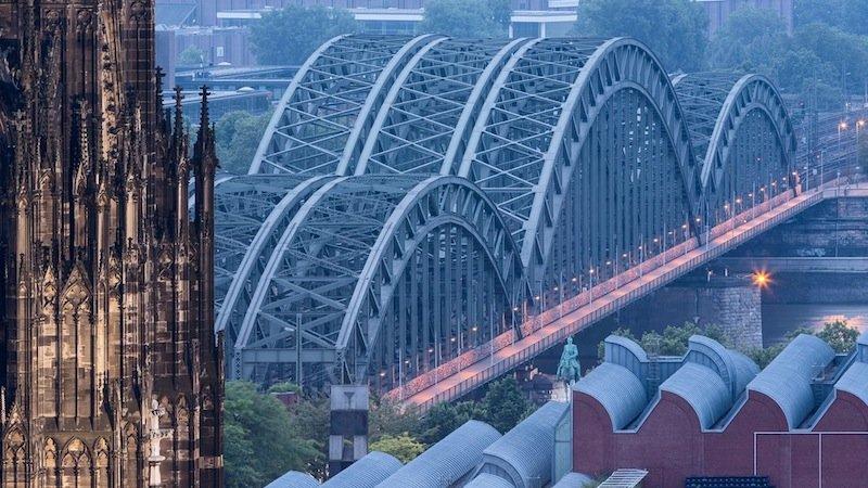 Die Hohenzollernbrücke mit der Kölner Messe im Hintergrund. Die Brücke wurde von 1907 bis 1911 gebaut, von der Wehrmacht 1945 gesprengt und 1948 wieder aufgebaut. In den 50er und in den 80er Jahren wurde sie auf sechs Gleise sowie um Geh- und Radwege erweitert. Eine Aufnahme aus 2013 von Hans-Georg Esch.