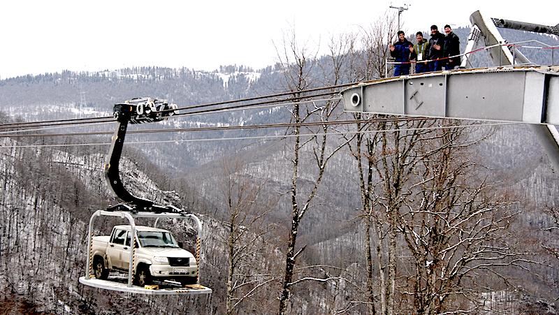 Doppelmayr-Mitarbeiter auf einem Stützpfeiler der Dreiseilbahn in Rosa Khutor. Die Anlage kann im Notfall sogar Autos und Mannschaftswagen in die Skigebiete transportieren. Dazu werden die Gondeln innerhalb einer Stunde abgekoppelt und durch Transportplattformen ersetzt.