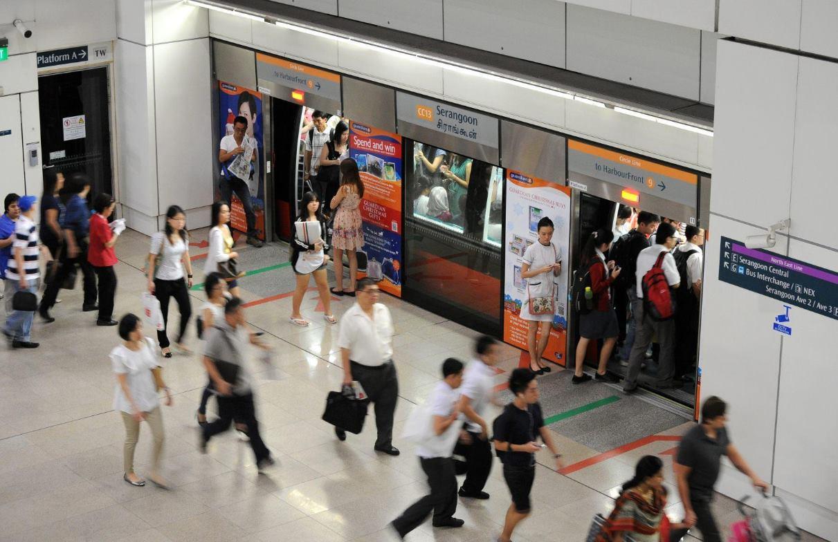 Fahrgäste steigen in die fahrerlose U-Bahn in Singapur:Die Bahnsteige werden von Bewegungssensoren überwacht, die Alarm auslösen, wenn Menschen bei der Einfahrt eines Zuges zu nah an die Bahnsteigkante treten oder gar auf die Gleise stürzen.