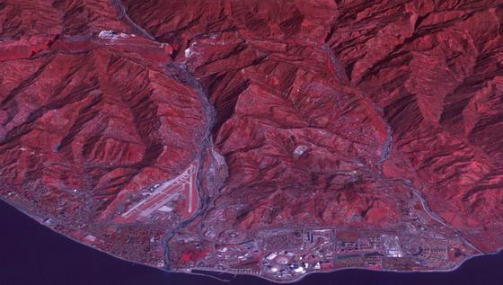 Dieses Bild eines NASA-Satelliten muss man übersetzen: Alles, was rot ist, ist Vegetation. Und die Berge sind in Wahrheit um etwa ein Drittel niedriger als es scheint. Das bisschen Weiß ist tatsächlich Schnee. Unten an der Küste erkennt man den Olympiapark mit den Hallen für Eishockey, Curling und Eiskunstlauf. Darin sitzen die Zuschauer in dicken Jacken, während sich draußen Touristen bei Temperaturen bis 19 Grad an den Strand legen oder gar ins Meer springen.