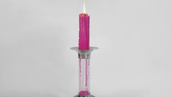 Der Kerzenhalter Rekindle Candle des Designers Benjamin Shine. Das Wachs tropft in ein Glasgefäß und härtet zu einer neuen Kerze aus. In der Mitte des Gefäßes hängt ein neuer Docht.
