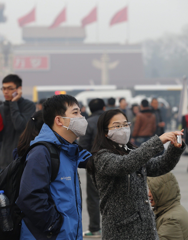 Ehepaar mit Maske auf dem Platz des Himmlischen Friedens in Peking: Die Luftverschmutzung in der chinesischen Hauptstadt hat neue Höchstwerte erreicht.