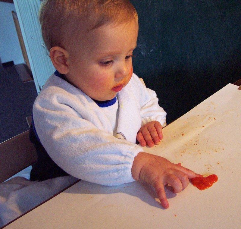 Die neuneinhalb Monate alte Lara schmiert konzentriert mit dem Zeigefinger mit einer leichten Wischbewegung.