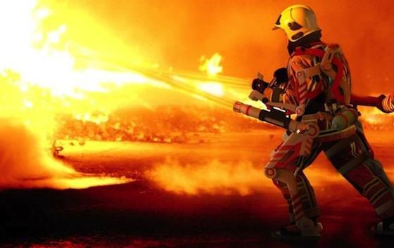 Der Feuerwehrmann der Zukunft streift sich ein Exoskelett über, mit dem er mühelos eine 90 Kilogramm schwere Ausrüstung die Treppe hinauftragen kann.
