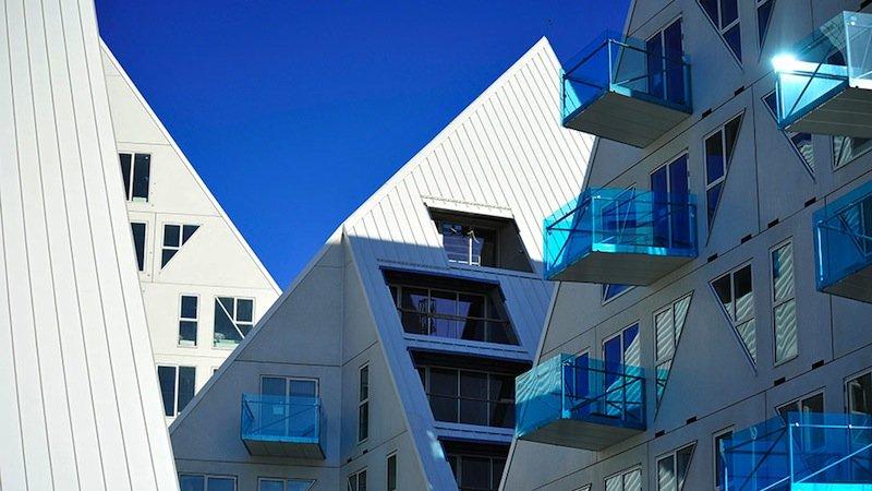 Möglichst viele Bewohner sollen Meerblick genießen können. Deswegen sind die Gebäude unterschiedlich hoch und die Dachflächen schrägt. Zum arktischen Ambiente passen auch die blau schimmernden Balkone.