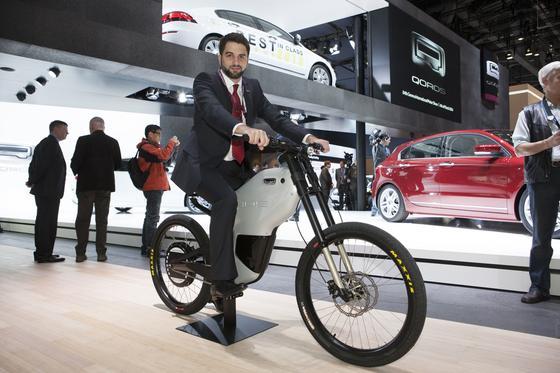 Vorstellung des eBIQUE auf dem Genfer Autosalon 2014. An der Entwicklung war die Marke Greyp von Rimac Automobili maßgeblich beteiligt. Rimac-Designer Adriano Mudri sitzt auch gut auf dem Qoros-Roller.