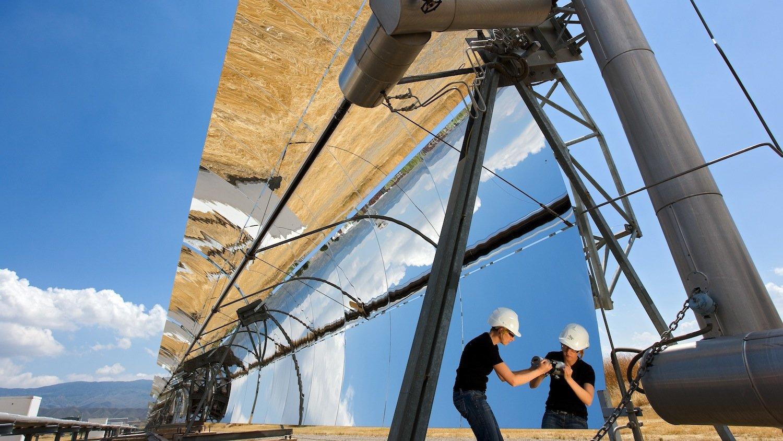 Parabolrinnenkollektoren fokussieren die Sonne linienförmig und lenken die Strahlen auf ein Receiverrohr. Dort erhitzen sie ein Wärmeträgermedium, das Dampf erzeugt, der wie in einem konventionellen Kraftwerk eine Turbine antreibt.