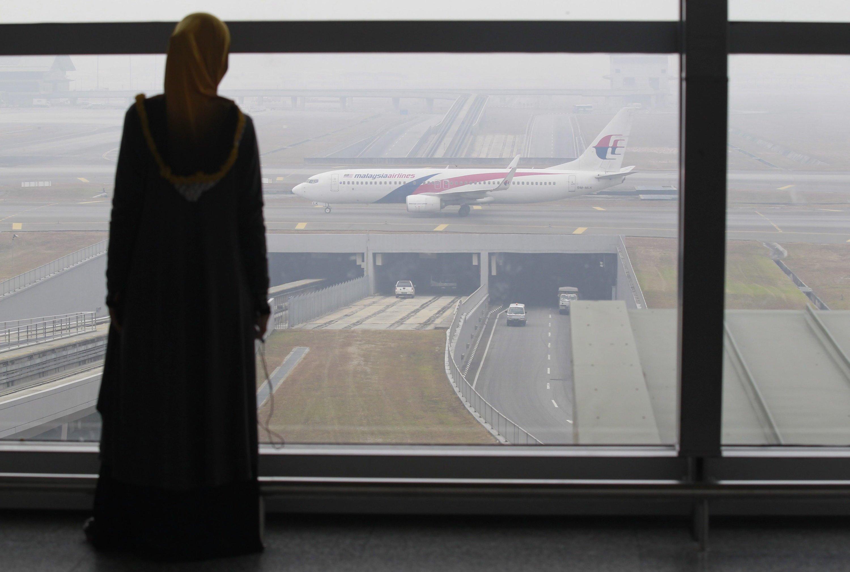 Eine Frau auf dem Flughafen von Kuala Lumpur schaut auf eine Maschine der Malaysia Airlines: Seit dem 8. März wird eine Boeing mit 227 Passagieren vermisst.