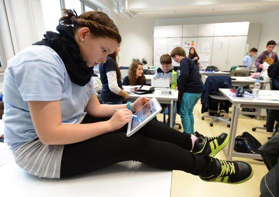 """Schülerin mit einem Tablet von Samsung: Angeblich lassen sich Daten von Samsung-Tablets und Smartphones über eine Sicherheitslücke von außen abrufen. Das Unternehmen hat inzwischen dementiert, dass es eine """"Hintertür"""" in der Software geben soll."""