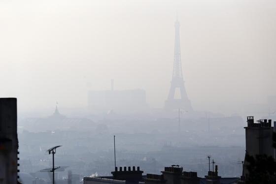 Der Pariser Eiffelturm im Smog: Mit Fahrverboten und Gratisfahrten in der Metro und mit Leihrädern reagiert Paris auf die zu hohe Feinstaubbelastung in der Stadt.