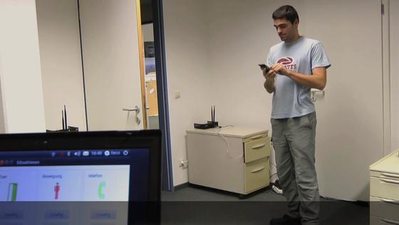 Der Computer im Vordergrund kann über die WLAN-Geräte im Raum überwachen, was der Mensch gerade tut. Auf dem Computerbildschirm ist markiert, dass der Mensch gerade steht und ein Telefon bedient.