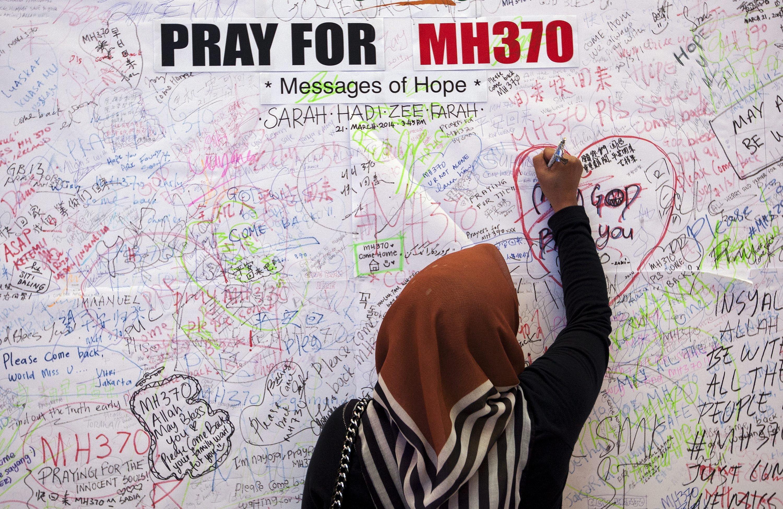 Eine Frau in Kuala Lumpur schreibt eine Botschaft der Hoffnung für die Opfer des Fluges MH370: Inzwischen ist klar, dass die Boeing der Malaysia Airways im Indischen Ozean abgestürzt ist.