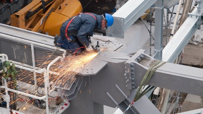 Arbeiter beim Bau des Rautendachs. Alle 38 Meter stützen massive Zwillingsstützen die 14 Rautenfachwerke.