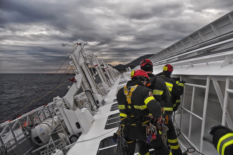 Ein Bergungsteam steht auf der seitlichen Bordwand des vor der toskanischen Insel Gigliohavarierten Kreuzfahrtschiffes