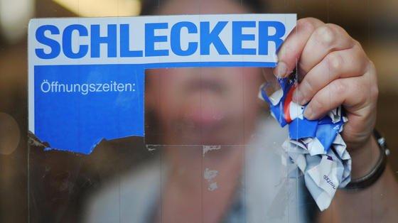 Schlecker-Mitarbeiterin reißt das Firmenlogo nach der Pleite der Drogeriemarktkette vom Schaufenster: Schlecker hatte seine Mitarbeiter unerlaubt überwacht und für ein schlechtes Betriebsklima gesorgt. Demotivierte Mitarbeiter kosten die Unternehmen in Deutschland nach einer Gallup-Studie jährlich 118 Milliarden Euro.