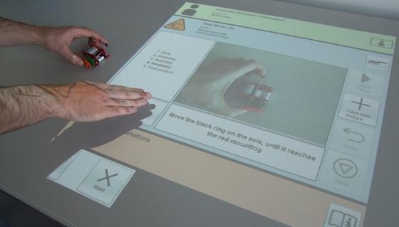 Das Assistenzsystem Promimo projiziert die Montageanleitung direkt auf die Arbeitsfläche. Der Arbeiter kann auch eigene Bewegungen filmen und speichern.