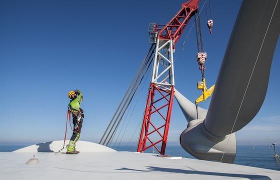 """Montage im Windpark Bard 100 Kilometer vor Borkum: Der Rotorstern wird mit dem Hauptkran eines Errichterschiffes auf die Gondel montiert, das sogenannte """"Sterneziehen"""". Dabei braucht es ruhige See und wenig Wind."""