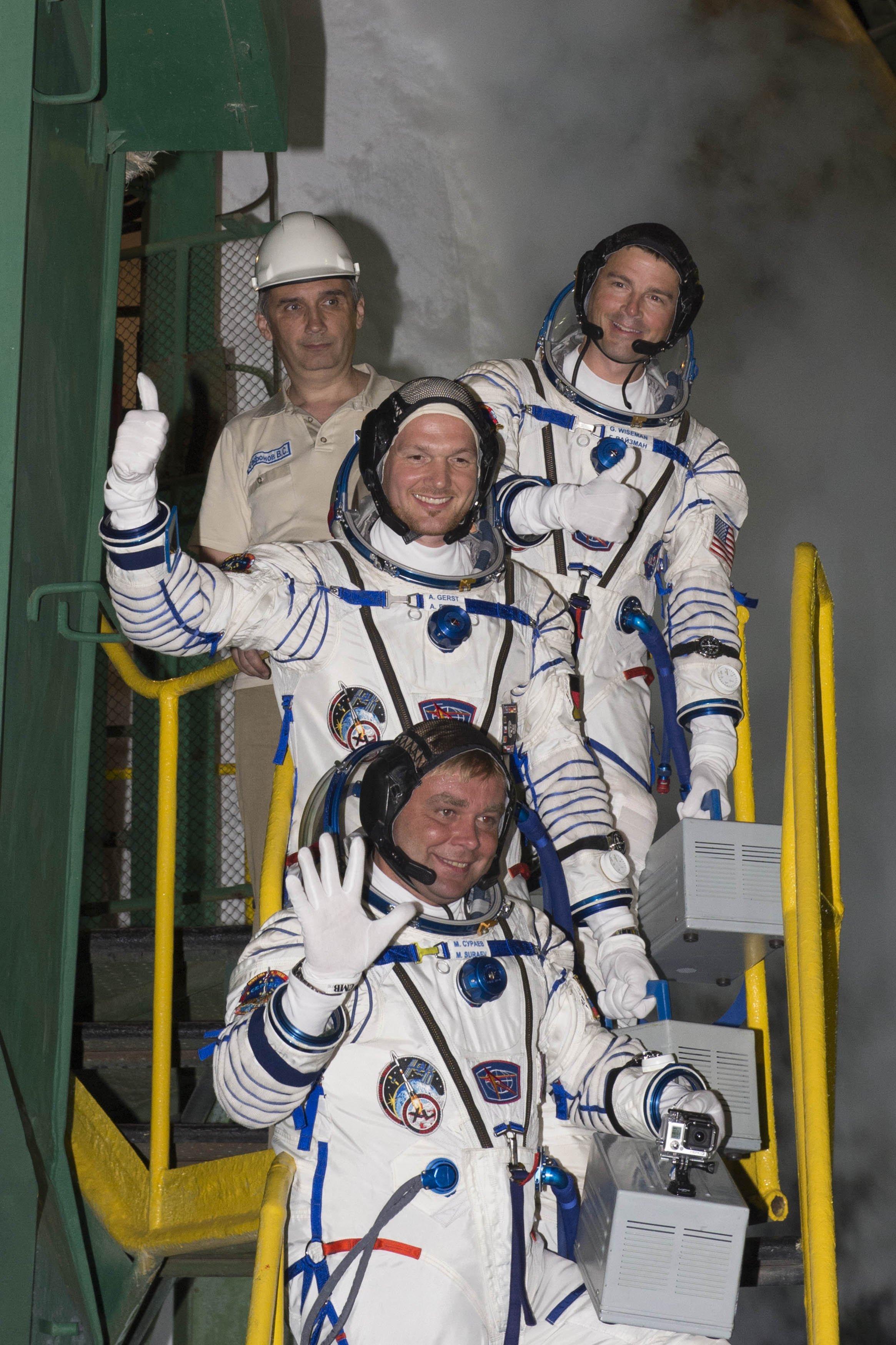 Auf geht's: der deutsche Astronaut Alexander Gerst (mitte), derrussische Kommandant Maxim Surajew (unten) und der amerikanische NASA-Astronaut Gregory Wiseman kurz vor dem Start derExpedition 40/41 auf der Treppe zur Sojus-Rakete auf dem Weltraumbahnhof Baikonur.