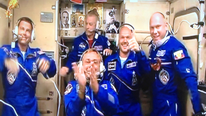 Glücklich angekommen: Nach einem sechsstündigen Express-Flug und einem rund zweistündigen Andockmanöver sind Alexander Gerst (2. von rechts), Reid Wiseman (links) und Maxim Surajew (Mitte) glücklich an Bord der ISS angekommen.