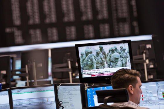 Aktienhändler an der Frankfurter Börse mit Bildschirm, auf dem ein Bericht über die Krimkrise läuft: Die Bundesbank erwartet keine größeren Auswirkungen der Krise auf die deutsche Wirtschaft.