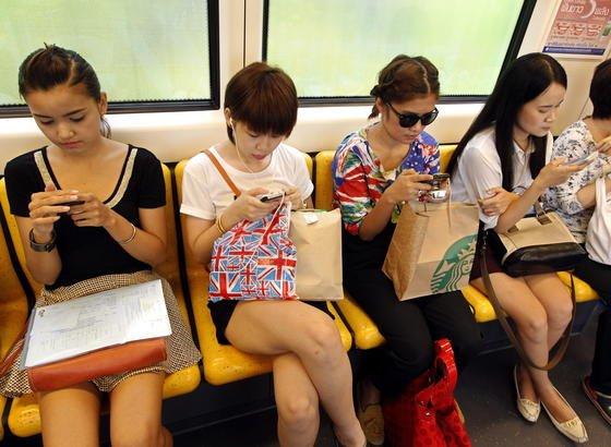Smartphone-Nutzer im Skytrain in Bangkok: Jetzt haben Forscher eine Technik weiterentwickelt, über die man etwa Smartphones über eine Distanz von bis zu fünf Metern kabellos aufladen kann.