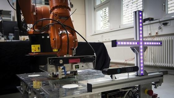 Kooperation intelligenter Maschinen: Der Robotergreifer übergibt ein Werkstück an eine bewegliche Plattform, die es zum nächsten Arbeitsschritt fährt.