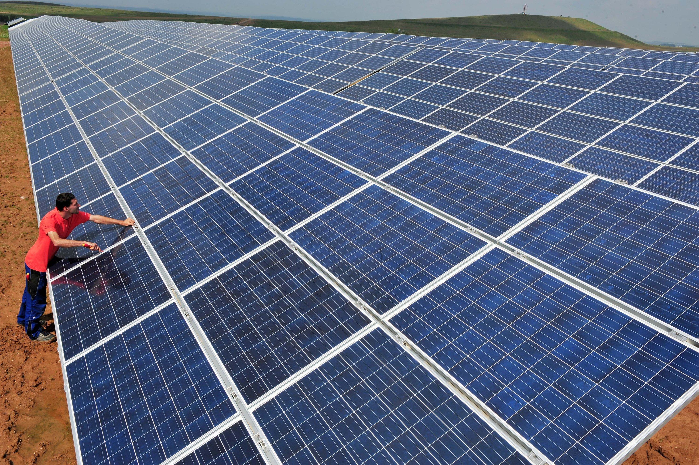 Ein Servicetechniker arbeitet in Ronneburg an den Solarmodulen in einem Solarpark, errichtet vom Unternehmen juwi Solar. Gerade bei solchen Großanlagen würde sich eine fünfprozentige Leistungssteigerung pro Modul auszahlen.