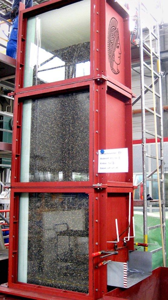 Öffnet sich die untere Klappe des drei Meter hohen Versuchsstandes, schießt ein Wasser-Kies-Gemisch aus dem Behälter heraus. Drucksensoren in den Seitenwänden messen die entstehenden Kräfte.