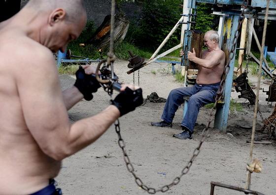 Ukrainische Männer trainieren in einem rustikalen Outdoor-Gym. Welche Möglichkeiten bieten Firmen in Deutschland ihren Mitarbeitern zur Gesundheitsförderung? Das will die Studie der Kölner Wissenschaftler nun herausfinden.