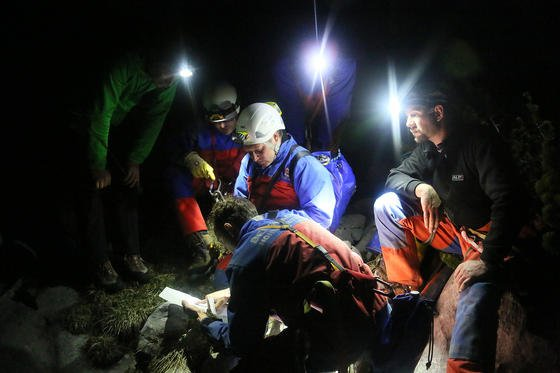 Einsatzkräfte der Bergwacht beraten das weitere Vorgehen am Untersberg in rund 1800 Metern Höhe beim Eingang in die Riesending-Schachthöhle. In rund 1000 Metern Tiefe sitzt hier in den Berchtesgadener Alpen der schwerverletzte Höhlenforscher fest.