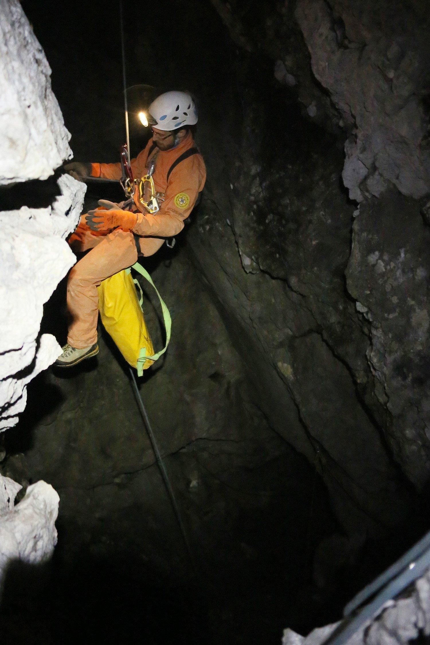 Ein Retter seilt sich in rund 1800 Metern Höhe am Eingang der Riesending-Schachthöhle ab. Der schwer verletzte Höhlenforscher befand sich zunächst in 1000 Meter Tiefe. Bei der aktuellen Bergungsetappe muss eine spiegelglatte Steilwand überwunden werden.