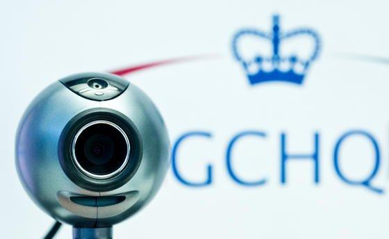 Eine Webcam vor dem Logo des britischen Geheimdienstes Government Communications Headquarters (GCHQ). Die britische Regierung hat zugegeben, dass ihr Abhördienst GCHQ im großen Stil den Internetverkehr wie etwa die Google-Suchen oder die Facebook-Aktivitäten britischer Bürger anzapft.