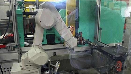 Die Spritzgießmaschine wird von einem Roboter bedient. Er entnimmt die Teile aus der Form, fährt verschiedene Prüf- und Bearbeitungsstationen an und legt sie schließlich auf einer Palette ab.