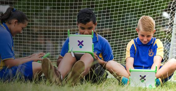 """Ist das die Zukunft? Diese kleinen Sportler sitzen im Gras und spielen mit einem Laptop. DieOrganisation """"One Laptop Per Child"""" will mit dem robusten Computer das Lernen in aller Welt verbessern."""