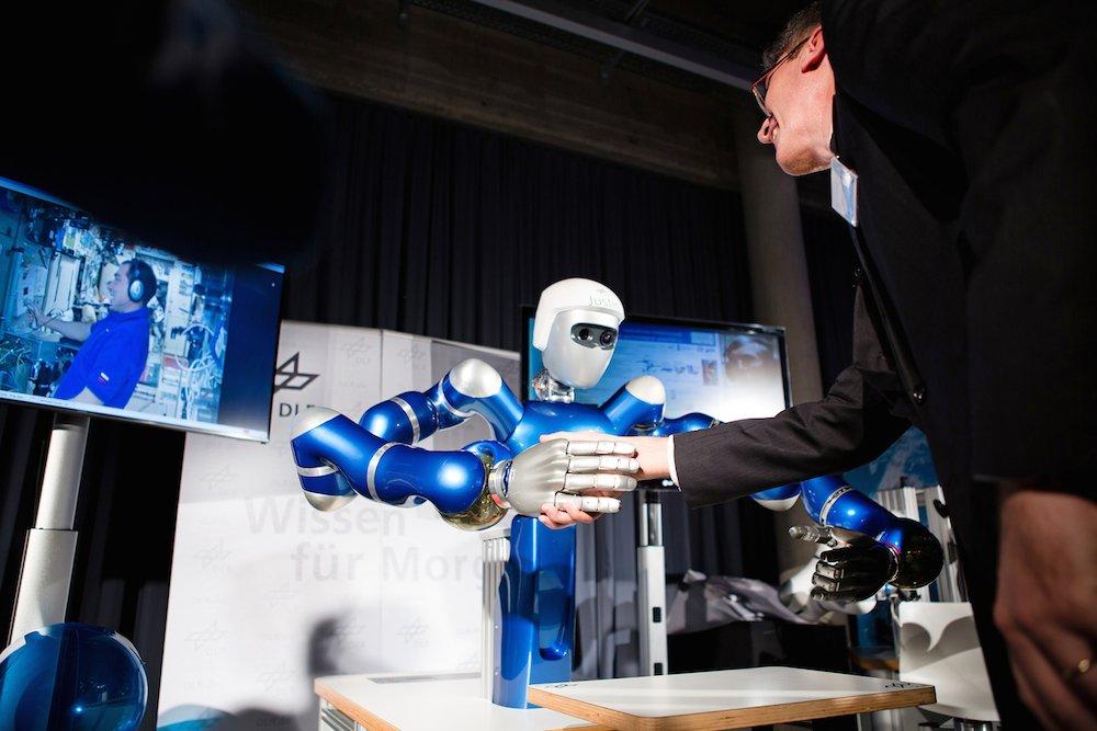 Kosmonaut Sergei Wolkow an Bord der ISS und DLR-Institutsleiter Prof. Alpin Albu-Schäffer schütteln sich in Oberpfaffenhoven die Hand – mittels des humanoiden Roboters SpaceJustin. Am 17. Dezember 2015 wurde erstmals ein humanoider Roboter aus dem All ferngesteuert.