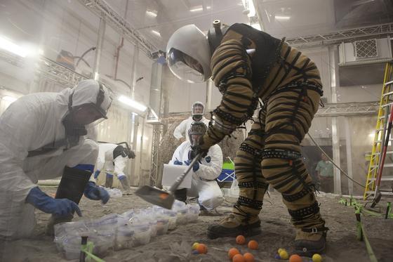 Der an der Universität von North Dakota entwickelte RaumanzugNDX-1 besteht aus superleichten Materialien und lässt dem Astronauten viel Bewegungsfreiheit. Beim Test zeigte sich, dass der Träger damit nicht nur losen Staub aufsammeln konnte, sondern auf auf dem Mars auch so beweglich wäre, dass er kleine Gesteinsbrocken ausgraben könnte. Neu entwickelte Geräte zum Sammeln von Proben haben die Wissenschaftler gleichzeitig mit dem Anzugtest durchgeführt.