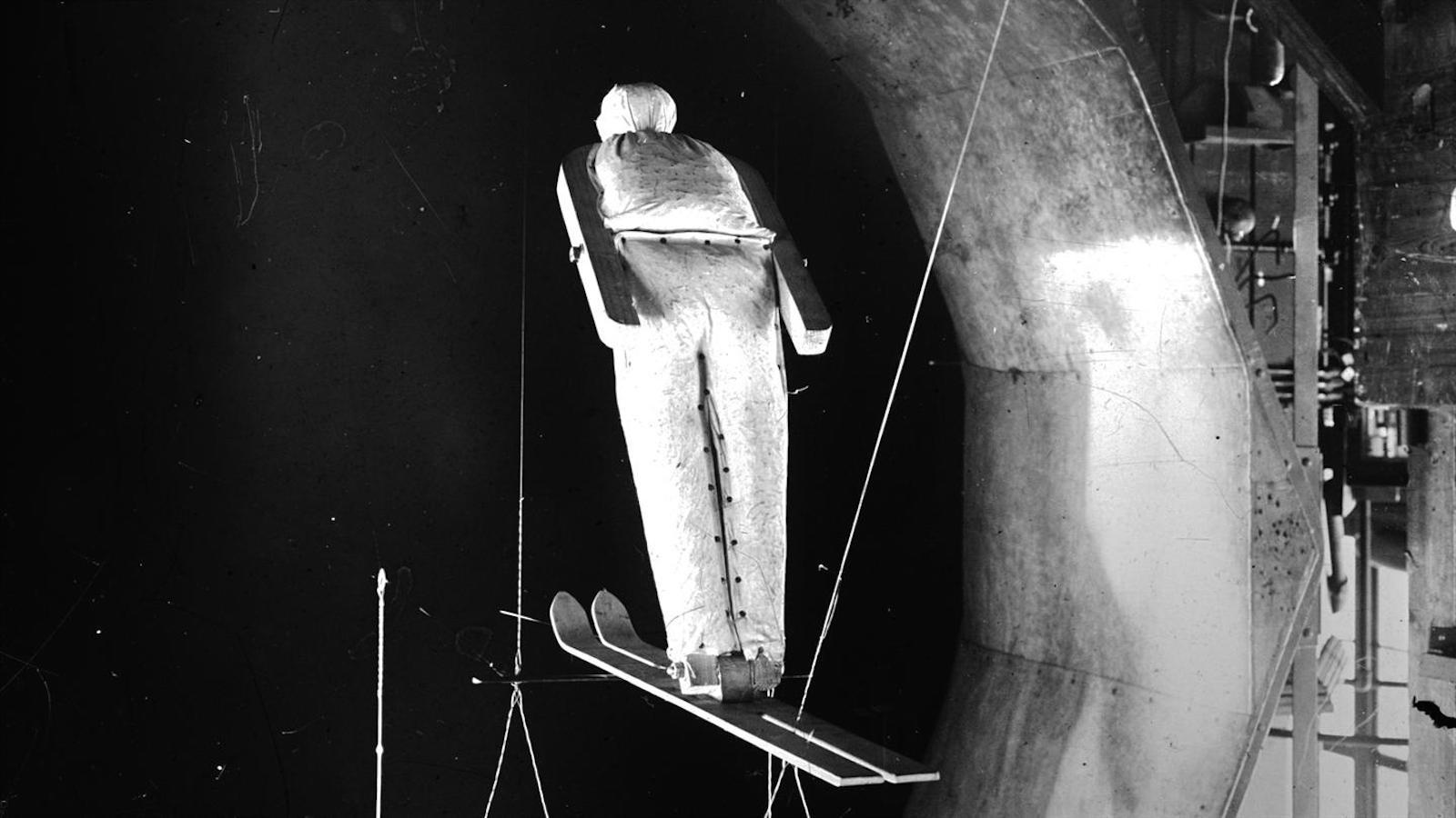 Aerodynamische Untersuchung eines etwa 50 Zentimeter großen Modells eines Skispringers in einem Windkanal der AVA-Göttingen, Vorläufer des heutigen DLR. Das Bild ist zur besseren Veranschaulichung verkehrt herum – eigentlich war die Puppe kopfüber aufgehängt.