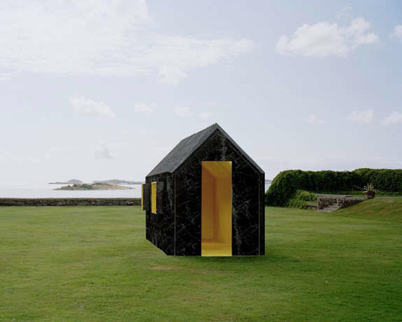 Die eine Außenseite der Dreiecke sowohl an den Seitenwänden als auch auf dem Dach ist weiß, die andere in schwarzer Marmor-Optik gehalten. Je nachdem, von welcher Seite man sich dem Häuschen nähert, erscheint es damit weiß, schwarz-marmoriert oder gestreift.