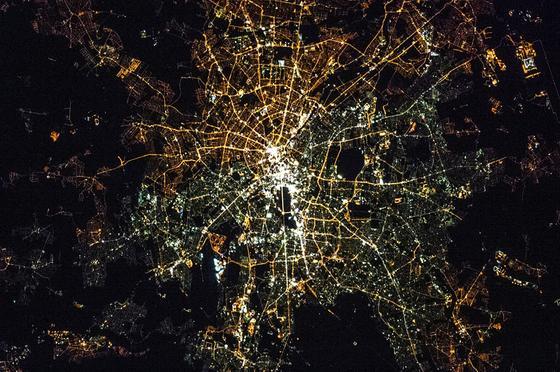 Berlin bei Nacht, fotografiert von der ISS: Im Westteil der Stadt leuchten vor allem weiße Quecksilber- oder auch LED-Lampen. Im Osten bestehen viele Straßenbeleuchtungen noch aus gelblichen Natriumdampflampen.