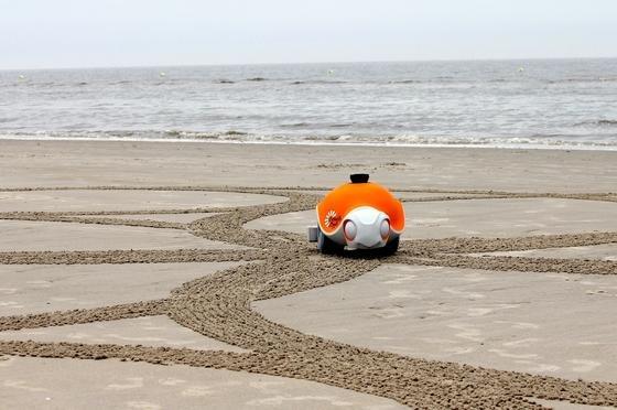 Der kleine Roboter BeachBot bei der Arbeit: Mit einem Rechen im Schwanz kann die rollendende Schildkröte Kunstwerke in den Sand zeichnen.