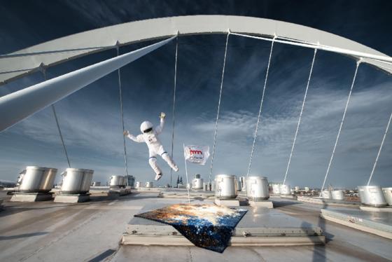 """Abgehoben: Der knotenreiche Teppich von Jan Kath""""Spacecrafted 3"""" mit sternenfunkelndem Weltraummotiv auf dem Dach der Kölner Lanxcess-Arena in Szene gesetzt."""