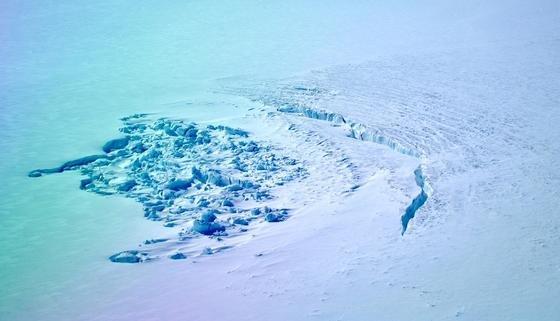 Das war mal ein Kratersee: Die Luftaufnahme vom April 2014 zeigt links im Bild den Krater, der kurz zuvor noch mit Wasser gefüllt war. Rechts deutlich zu sehen durch großen Risse im Eis, durch die große Wassermassen an den Grund der Gletscher fließen kann.