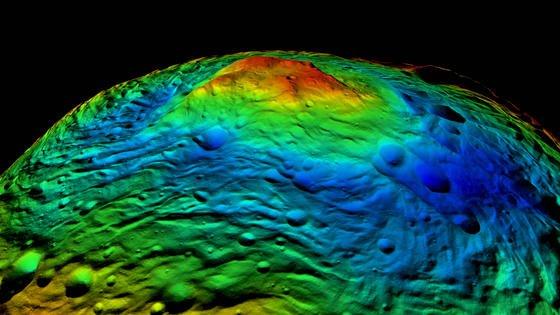 Der Südpol von Vesta: Vor ihrem Weiterflug zum Zwergplaneten Ceres hat die Raumsonde Dawn den Planeten Vesta aufgenommen. Die perspektivische, in Falschfarben dargestellte Topographie des Südpols von Vesta zeigt in blauen Farbtönen Teile des 500 Kilometer großen Rheasilvia-Beckens mit einem über 20 Kilometer hohen Bergmassiv in grünen, gelben und roten Tönen.