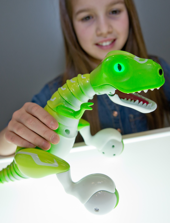 Die kleine Nina spielt auf der Messe mit dem Zoomer Dino von Spin Master International.