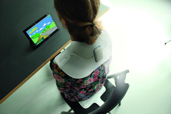 Contergan-Geschädigte bei Fitness-Übungen: Sie steuert einen Avatar über ihre Körperbewegungen, die von den Sensoren eines Schulter- und eines Sitzkissens erfasst werden.