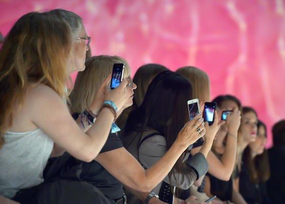 Junge Frauen filmen mit ihren Smartphones auf der Modenschau von Miranda Konstantintinidou bei der Mercedes-Benz Fashion Week in Berlin: Jugendliche nutzen elektronische Geräte inzwischen so intensiv, dass sie unter Schlafstörungen leiden.