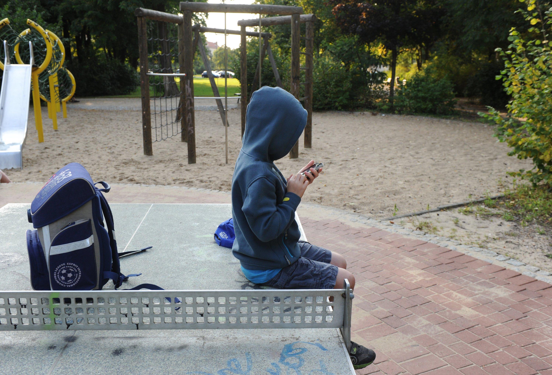 Kind mit Smartphone auf einem Kinderspielplatz in Berlin: Das Telefon ist längst zum unverzichtbaren Begleiter auch von Kindern geworden. Selbst kurz vor dem Schlafen wird das Gerät benutzt. Die Folge: Manche Kinder schlafen nur noch fünf Stunden pro Nacht.