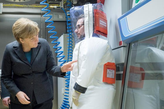 Ein kritischer Blick auf den Schutzanzug von RKI-Mitarbeitr Fran Siejak: Bundeskanzlerin Angela Merkel bei der Eröffnung des neuen S-4-Hochsicherheitslabors im Robert Koch-Institut in Berlin.